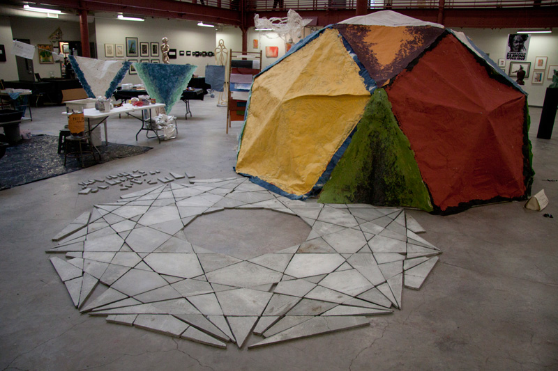 Dome<br>Inspired by Buckminster Fuller's domes we cast paper on onto a dome viewers could enter. The cement relief sculpture on the floor was completely conceived and made by James.